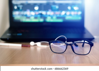 Glasses for filtering blue light from the computer.This helps prevent Computer Vision Syndrome.Glasses for computer work and headset,Notebook,on desk.