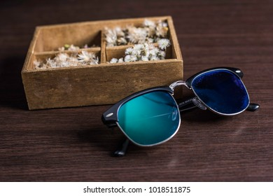 Glasses and flower box on table wood background.