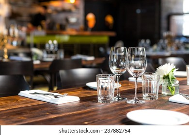 Glasses, flower fork, knife served for dinner in restaurant with cozy interior
