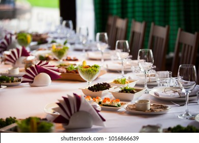 Glasses, flowers, fork, knife served for dinner in restaurant with cozy interior