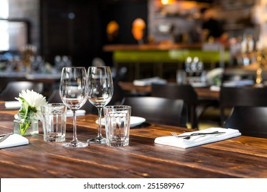 Glasses, flowers, forks, knives served for dinner in restaurant with cozy interior.