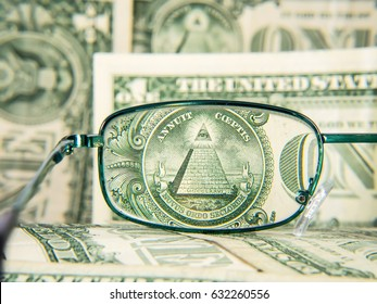 Glasses focused on dollar banknote, dollar money with pyramid and eye, detail