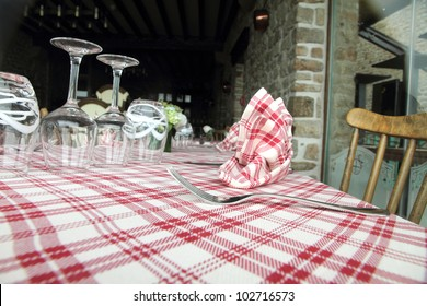 Glasses, fork and knife on red and white checked gingham tablecloth