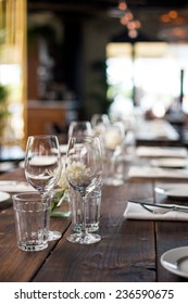 Glasses, forks, knives, napkins and decorative flower on a dark old brown wooden table served for dinner in cozy restaurant
