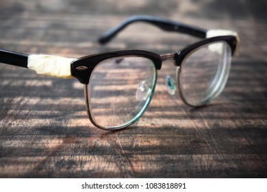 Glasses frame made of black plastic. The legs are wrapped with masking tape.The old glasses in damage and broken.