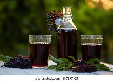 Glasses of fresh elderberry syrup and elderberries on a wooden table
