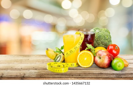 Glasses of fresh juice and fruits with vegetables and measuring tape
