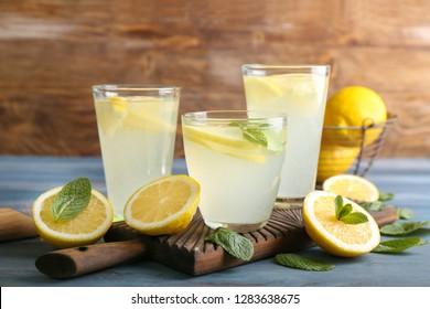 Glasses of fresh lemonade on wooden table