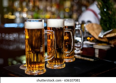 Glasses of fresh light draft beer. Evening in the bar. Vacation with friends. Beautiful blurred background in the side