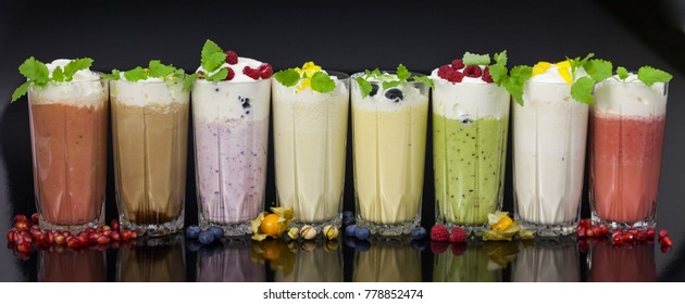 glasses of fresh milk cocktails (chocolate, strawberry, vanilla, kiwi, blueberry, pomegranate)  with fruits and berries on black background