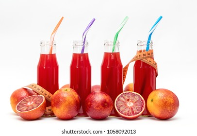 Glasses of fresh pressed blood orange fruit juice with tape measure isolated on white background. Healthy fitness lifestyle concept.