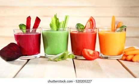 Glasses with fresh vegetable smoothie on wooden table