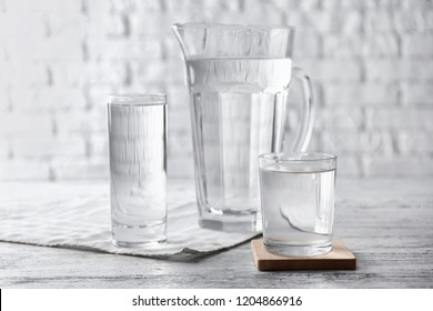 Glasses of fresh water and jug on light table