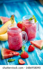 In glasses, freshly squeezed juice from strawberries, watermelon, banana and mint next to a strawberry berry piece of watermelon ljyatyat and banana on a wooden blue background