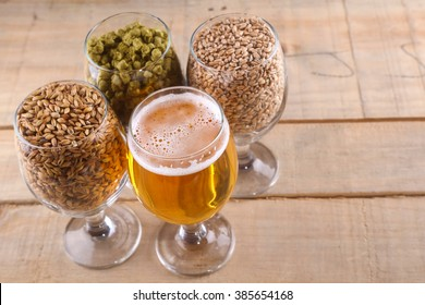 Glasses full of light beer, different types of malt and hops over a wooden background