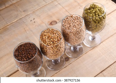 Glasses full of malts and hops over a wooden background