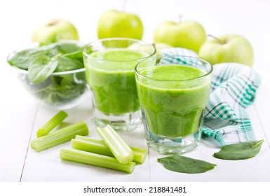 glasses of green juice with apple and spinach on wooden table