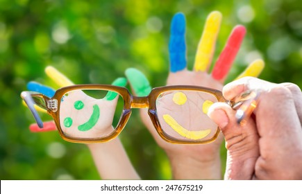 Glasses in hand. Smiley on hands against green spring blur background