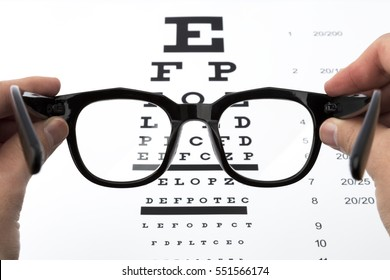 Glasses in hands, eyesight-test chart isolated on white background