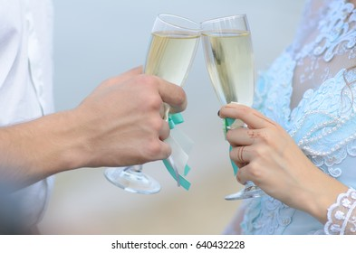 The glasses in the hands of the newlyweds