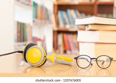 glasses and headphones as audio books concept on  high school or university library background