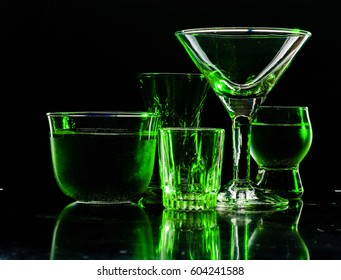 Glasses and glasses highlighted by colored light on a black background. Low key.