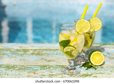 Glasses of homemade lemonade on a rustic wooden blue background.