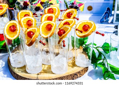 Glasses of ice cubes decorated with fruits, ready to be filled with mocktail or cocktail drinks.