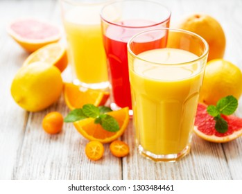 Glasses of juice and citrus fruits on a wooden table