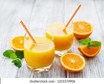 Glasses of juice and orange  fruits on a wooden table
