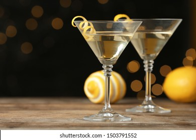 Glasses of Lemon Drop Martini cocktail with zest on wooden table against blurred background. Space for text