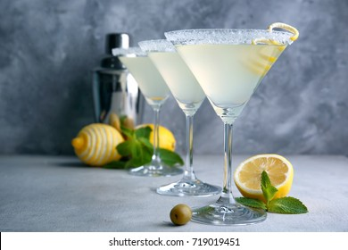 Glasses of lemon drop martini with zest on table