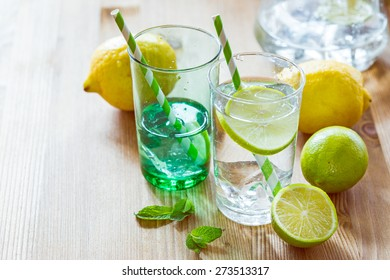 Glasses of lemonade with striped paper straws with mint leaves and fresh lime