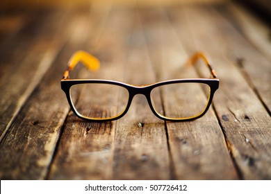 glasses  lie on the dark wooden table.   Black orange  glasses on wooden table. Office workplace with glasses on wood table. Glasses with orange rim. Orange Case for storage points.