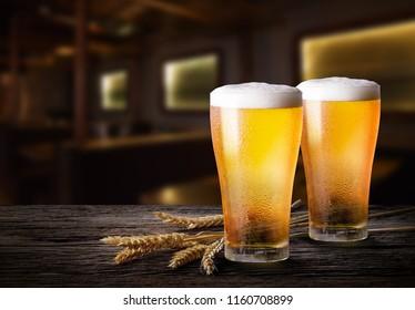 Glasses of light beer with barley at bar