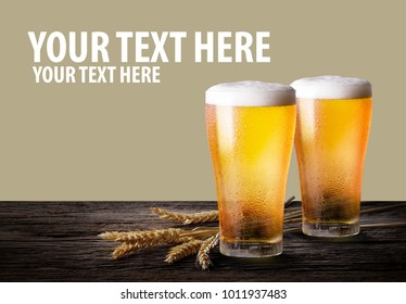 Glasses of light beer with barley on the khaki color background with copy space.
