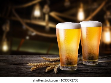 Glasses of light beer with barley on wooden table with copy space