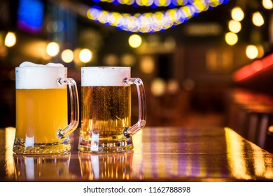 Glasses of light beer on a pub background.