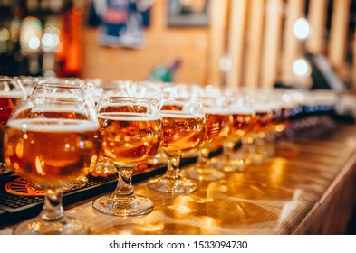 Glasses of light beer on wooden bar counter. Pub blurred background