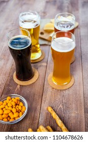 glasses of light and dark beer with assorted snacks on a wooden table background. bachelor party, pub, bar or degustation concept