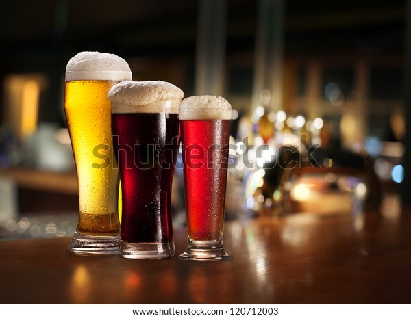 Glasses of light and dark beer on a pub counter. Beer background.
