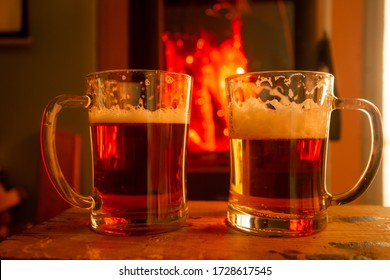 Glasses with light fresh beer on the background of the fireplace