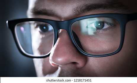 Glasses with light reflected from computer or smartphone screen. Thoughtful business man or focused student working late at night. Coder, programmer or geek with phone or laptop. Reflection of monitor