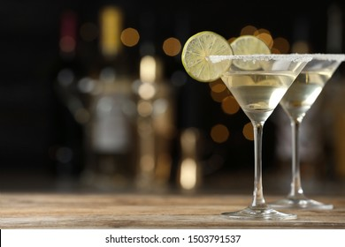 Glasses of Lime Drop Martini cocktail on wooden table against blurred background. Space for text