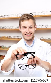 Glasses. The man chooses spectacle frames in the optical salon