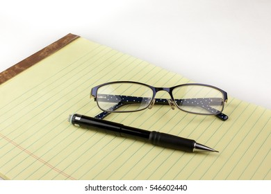 Glasses and mechanical pencil on legal pad