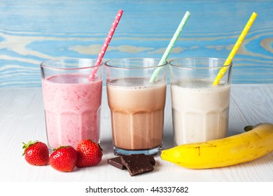 Glasses of milkshakes with chocolate, strawberry, banana flavor, with ice cream on wooden blue and white background. Sweet drinks for summer concept. Shakes and smoothies. Milk shake and cocktail.