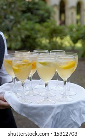Glasses of mimosa being served at formal party