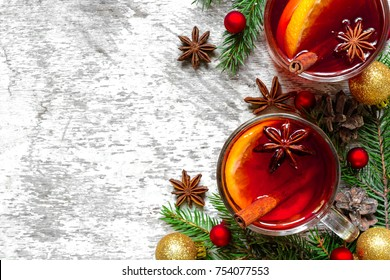 glasses of mulled wine with cinnamon, anise and fir tree branches with decorations on white wooden background with copy space. top view. winter christmas drink