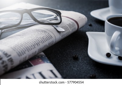 Glasses and newspaper and cup of coffee on black stone background